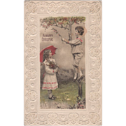 Boy in a Tree Handing Branch to a Girl with Umbrella Vintage Christmas Postcard