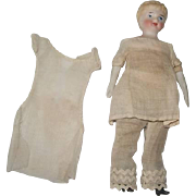 Antique bisque doll house doll in original underclothes. Painted face, bisque arms & legs, clo