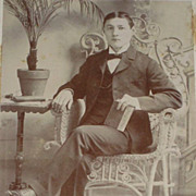 Antique Victorian Cabinet Card of Well Dressed Young Man Sitting in Wicker Chair holding a ...